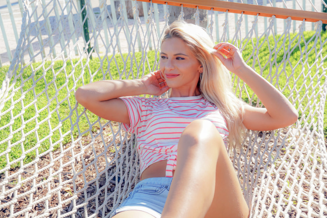 Allie Severino laying in hammock wearing shorts and red and white stripped shirt blonde hair
